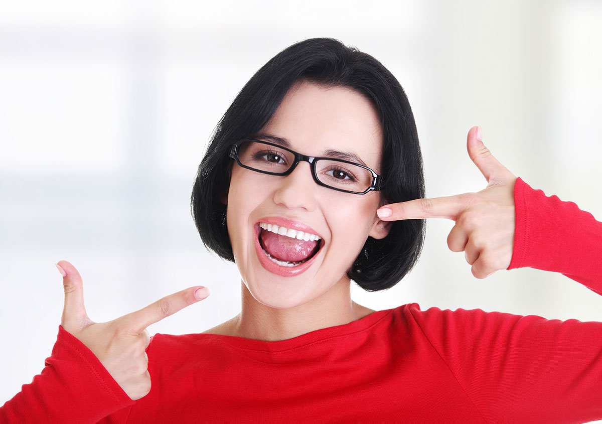 Woman pointing finger at her teeth